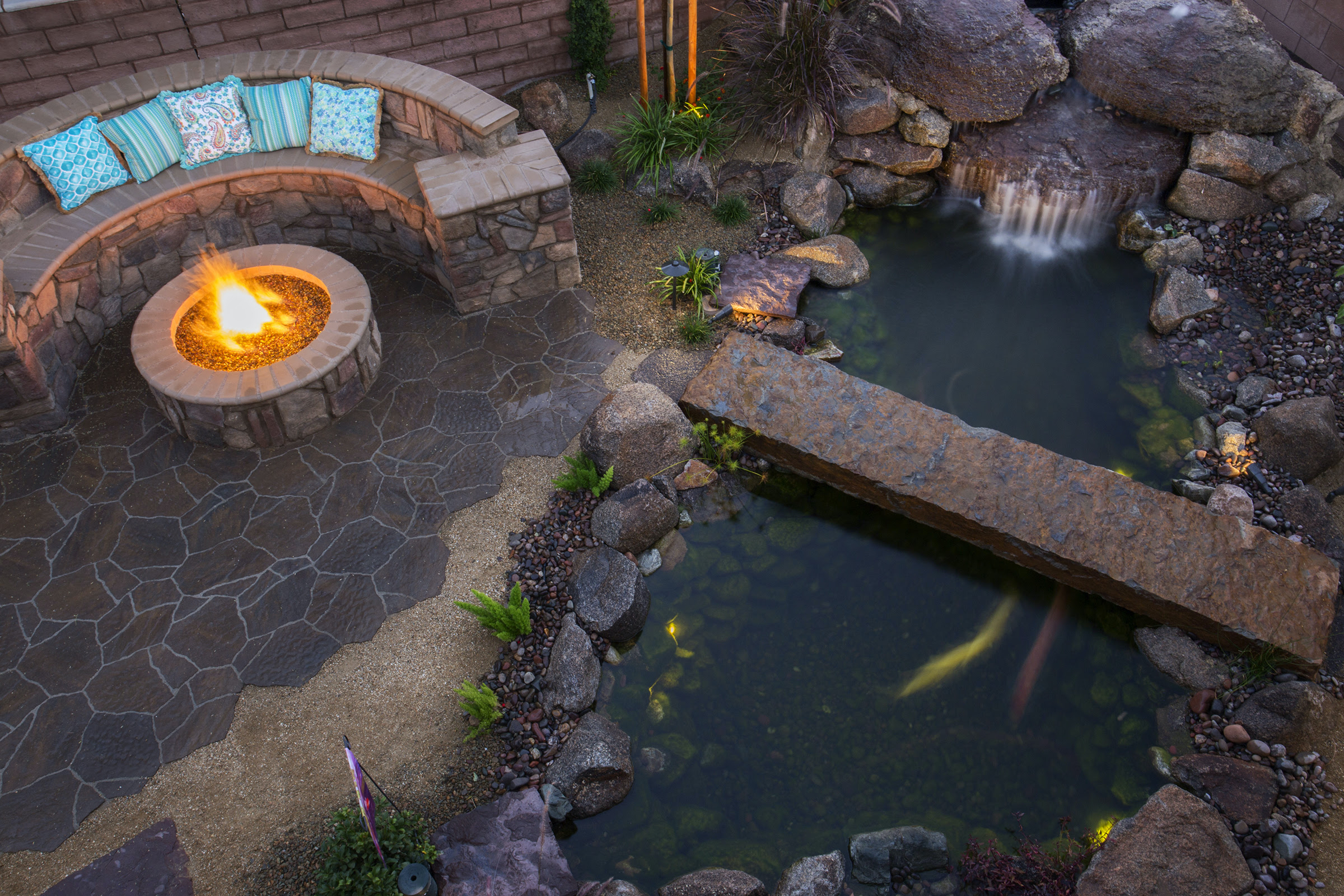 A beautiful backyard koi pond with a bridge, fire pit, and custom hardscapes.