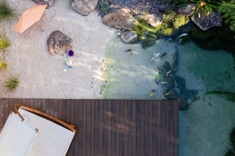 Beachfront swimmable koi pond with sand, koi fish and a floating deck.